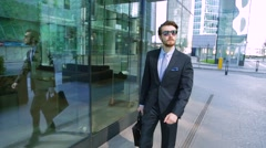 Businessman in sunglasses is walking down the street near the office center Stock Footage