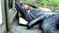 Drunk man waking up while lying on the ground and looking around, steadycam shot Stock Footage