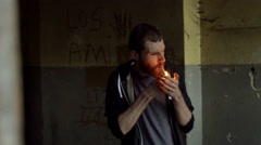 Pensive man standing in the abandoned building and smoking cigarette, steadycam Stock Footage