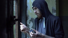 Sad man standing in the abandoned building and burning matches, steadycam shot Stock Footage
