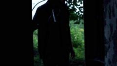 Man in hood walking inside abandoned building, steadycam shot Stock Footage