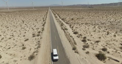AERIAL: White Truck Driving Desert Highway Stock Footage