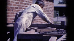 1968: man in jumpsuit repeatedly scoops paste onto surface using a trowel Stock Footage