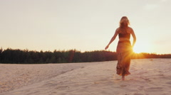 Young woman in a beautiful dress light runs along the beach into the sunset Stock Footage
