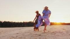 Two women in light dresses run toward the sun. Concept: women's dreams, health Stock Footage