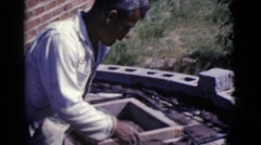 1968: a man spreading cement on a flat curved surface with a hand tool Stock Footage