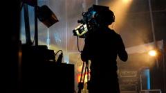 Cameraman on stage. Guitar player partially hidden. Dark silhouette. Stock Footage