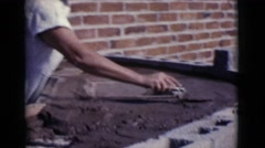 1968: a female is seen placing cement and building something COTTONWOOD, ARIZONA Stock Footage