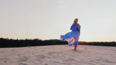 Steadicam slow motion shot: A young woman in a light dress-air runs at sunset on Stock Footage