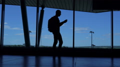 Young man with a backpack standingat ufa airport lounge and talking on the phone Stock Footage