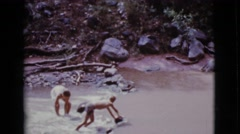 1968: two children standing in a river throwing rocks and building a damn Stock Footage
