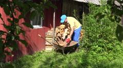 Garden worker man boy unload firewood wood from rusty wheelbarrow. 4K Stock Footage