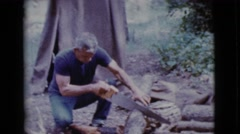 1968: a man cutting wood to prepare food COTTONWOOD, ARIZONA Stock Footage