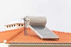 Hot water boiler with solar panel on roof Stock Photos