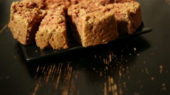 Girl's hand takes a piece of oat cake from black plate on a black table. Stock Footage
