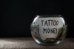 Glass jar witn money for tattoo Stock Photos
