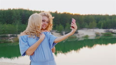 Steadicam shot: Two attractive women in dresses make selfie on the background of Stock Footage