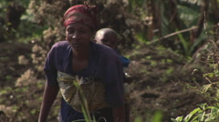 Tracking-out of an African woman climbing a green hill with her baby on her Stock Footage