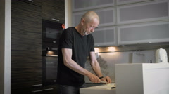 The man at the age of preparing a meal in their modern kitchen Stock Footage