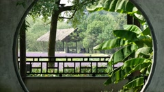 Chinese lavender garden through circular hole in wall Stock Footage