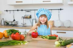 Portrait of a pretty little girl in cook clothes on a kitchen Stock Photos