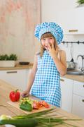 Portrait of little girl in cook clothes smiles behind a table on a kitchen Stock Photos