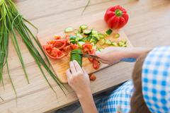 TOP VIEW: Little girl in cook clothes cuts a cucumber on a board on a kitchen Stock Photos