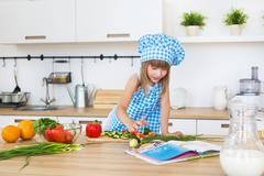 Pretty little girl in cook clothes reads a recipe book on a kitchen Stock Photos