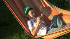 Boy relaxes in a hammock and using mobile phone Stock Footage