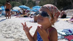 Little girl face portrait have fun on beach wearing adult swimming mask glasses Stock Footage