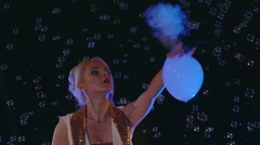 Female actor inflates bubbles with grey smoke and plays with them. Stock Footage