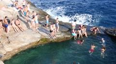 People in Greece resort Thassos Giola swim jump in nature sea bath from rocks Stock Footage