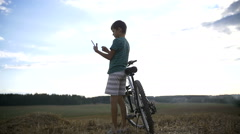 Boy with bicycle uses the phone on the mountain Stock Footage