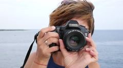 Female photographer shoot take pictures photo of sea nature camera lense shutter Stock Footage
