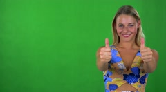 Young pretty blond woman shows thumbs up on agreement - green screen - studio  Stock Footage