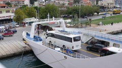 Greece, Keramoti - ferry boat arrival from island Thassos tourist buses move out Stock Footage