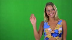 Young pretty blond woman waves with hand - green screen - studio  Stock Footage