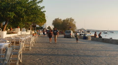 Boulevard of Greek fishing village in early evening sun Stock Footage