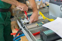 Electrician assembling industrial electric cabinet. Stock Photos