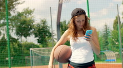 Sporty girl holding ball and using smartphone while standing on sports field Stock Footage