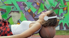 Girl lying on the ball and listening music while having a nap Stock Footage