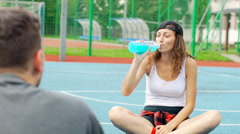 Girl throwing ball to someone and drinking energy drink on sports field Stock Footage