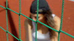 Girl sitting behind net and looking thoughtful, steadycam shot Stock Footage