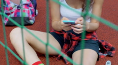 Girl sitting on sports field behing net and texting on smartphone, steadycam sho Stock Footage