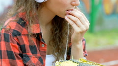 Girl listening music on headphones and eating sunflower's seeds Stock Footage