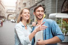 Positive loving couple standing in the street Stock Photos