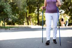 Elderly woman running in the park with sprinter sticks Stock Photos
