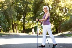 Grey-haired woman walking with tracking sticks in the park Stock Photos