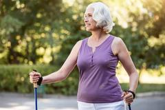 Happy pensioner woman having a walk during sunny day Stock Photos