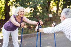 Nice old lady exercising opposite her husband Stock Photos